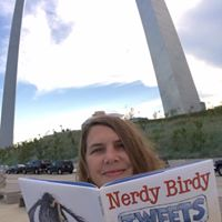Ms. Cobb reading a book in front of the Arch